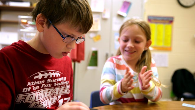 Nick Teska, a second-grader at Neenah's Tullar Elementary School with autism spectrum disorder, plays a game on an iPad while Jenna Clark cheers him on during their Power of Peer Support group session.