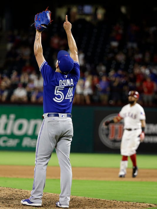 Toronto Blue Jays' Roberto Osuna celebrates on the mound after getting Texas Rangers' Rougned Odor, rear, to fly out for the final out in the ninth inning of a baseball game, Monday, June 19, 2017, in Arlington, Texas. The Blue Jays won 7-6. (AP Photo/Tony Gutierrez)