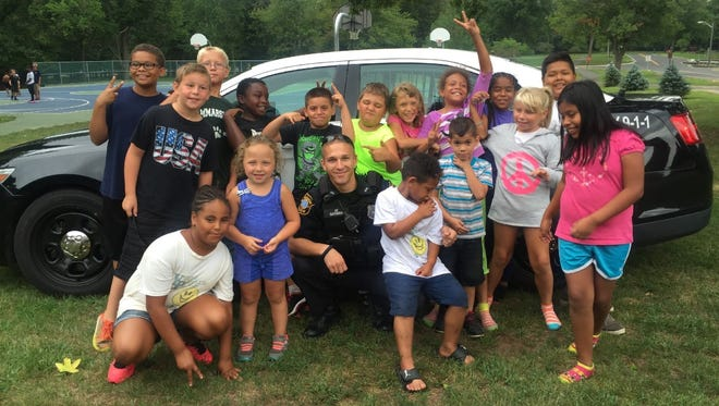 """Edison Police Officer Christopher Gadomski (center) is surrounded by some of the township's """"cool kids."""""""