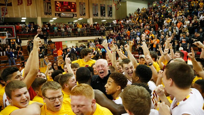 Head coach Rick Peckinpaugh, center, and the rest of the Mavericks are mobbed after McCutcheon defeated Warsaw 40-37 in the Class 4A Semi-State Saturday, March 19, 2016, at Lafayette Jeff High School. McCutcheon advances to the state finals.