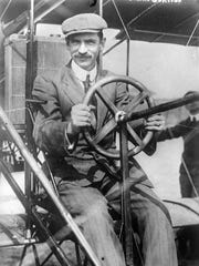 Glenn Curtiss at the pilot's wheel of his biplane.