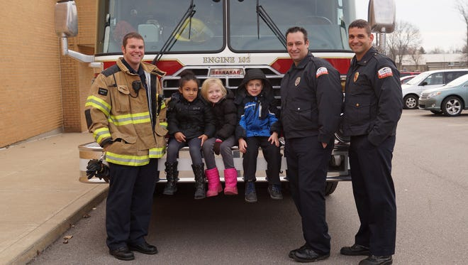 Kiera Cottrell, Kendal Hager and Max Nezi, kindergartners at Florence Elementary, posed for a picture on engine 102 with the Florence fire fighters, Ryan Born, Will Clark and officer Steve Shrek. The fire fighters talked with all the kindergartners on fire safety.