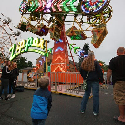 Finnegan Murphy, 4, looks on at the Zipper, hoping he is tall enough next year to ride it.