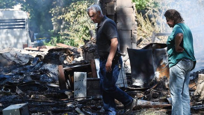 Lisa Ann Butitta, right, and Capt. Bill Hilligoss of the Marion County Sheriff's Office look over the burnt remains of Butitta's house on County Road 6084 in rural Marion County on Wednesday.