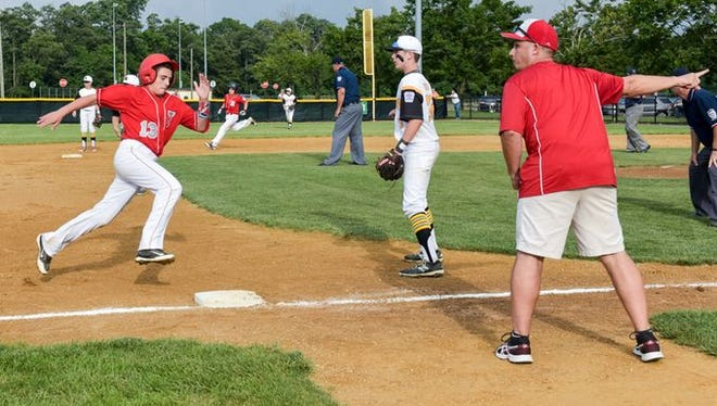 Holbrook's Dallas Weisse (13) races around third at the direction of his manager Art Bonitz during Monday afternoon's game against Bordentown
