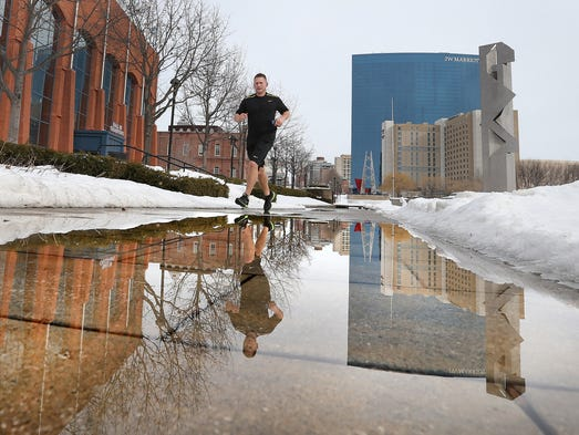Joggers take advantage of the warm temperatures to get out and run through the flooded sidewalks in the White River State Park Tuesday afternoon.