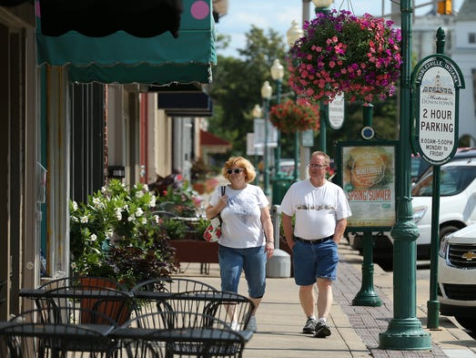 Tom and Tammy Edgreen, of Anderson, walk along the courthouse square, Thursday, July 17, 2014, in downtown Noblesville.