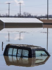 The cab of a pickup truck peeks out of floodwaters