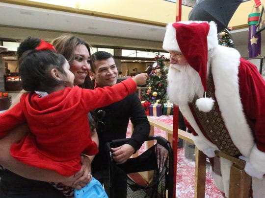 Angie De La Cruz holds daughter Jazlyn De La Cruz, 2, as the little girl offers Santa Clause a bite out of her candy during a visit last week to Cielo Vista Mall. Also watching was friend Anthony Rodriguez.