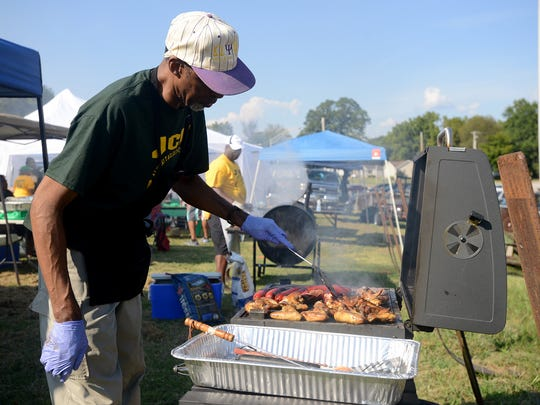 Alvino Douglass, Jackson Central-Merry Class of 1974, grills chicken during a JCM all-alumni tailgating event Friday.