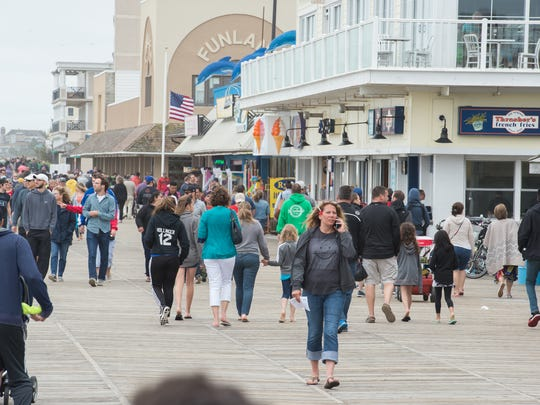 Visitors to Rehoboth Beach walk next to shops along