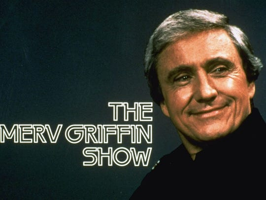 Talk show host Merv Griffin appears beside his television