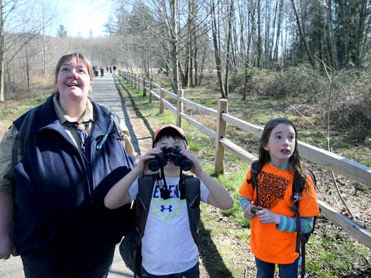 Pack 5239 Den leader Traci Siasat, left, looks at a hawk flying on the Clear Creek Trail with Tiger Scouts, Trygger Carter, 6, and Annabeth Taylor, 7.
