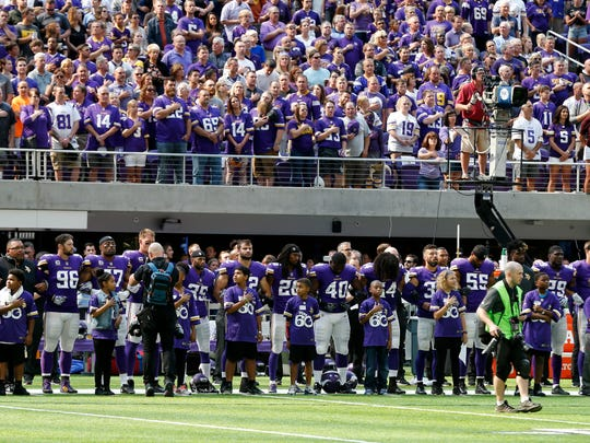 Minnesota Vikings players lock arms during the playing of the national anthem before an NFL football game against the Tampa Bay Buccaneers, Sunday, Sept. 24, 2017, in Minneapolis.