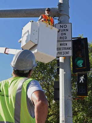City workers install a new right-turn sign at the corner of 10th Street and Minnesota Avenue on Tuesday morning. Starting Tuesday, drivers are allowed to make right turns on red lights at two of the Sioux Falls' busiest intersections, Minnesota Avenue at 10th and 11th streets. City traffic officials said the changes are intended to improve traffic flow.