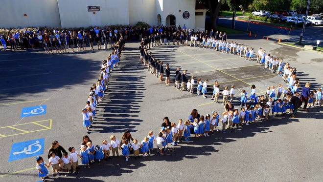 Students from St. James Episcopal School gather to make a 70 as they celebrate their 70th anniversary on Thursday, Sept. 29, 2016, in Corpus Christi.