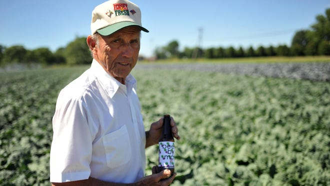 John Formisano stands at his farm with a bottle of Beets by May, a craft beer made by Cape May Brewing Company using his beets.