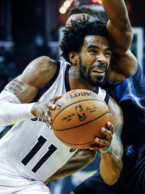 Grizzlies guard Mike Conley (left) drives for a layup against Dallas Mavericks defender Yogi Ferrell (right) during the second quarter Tuesday at FedExForum.