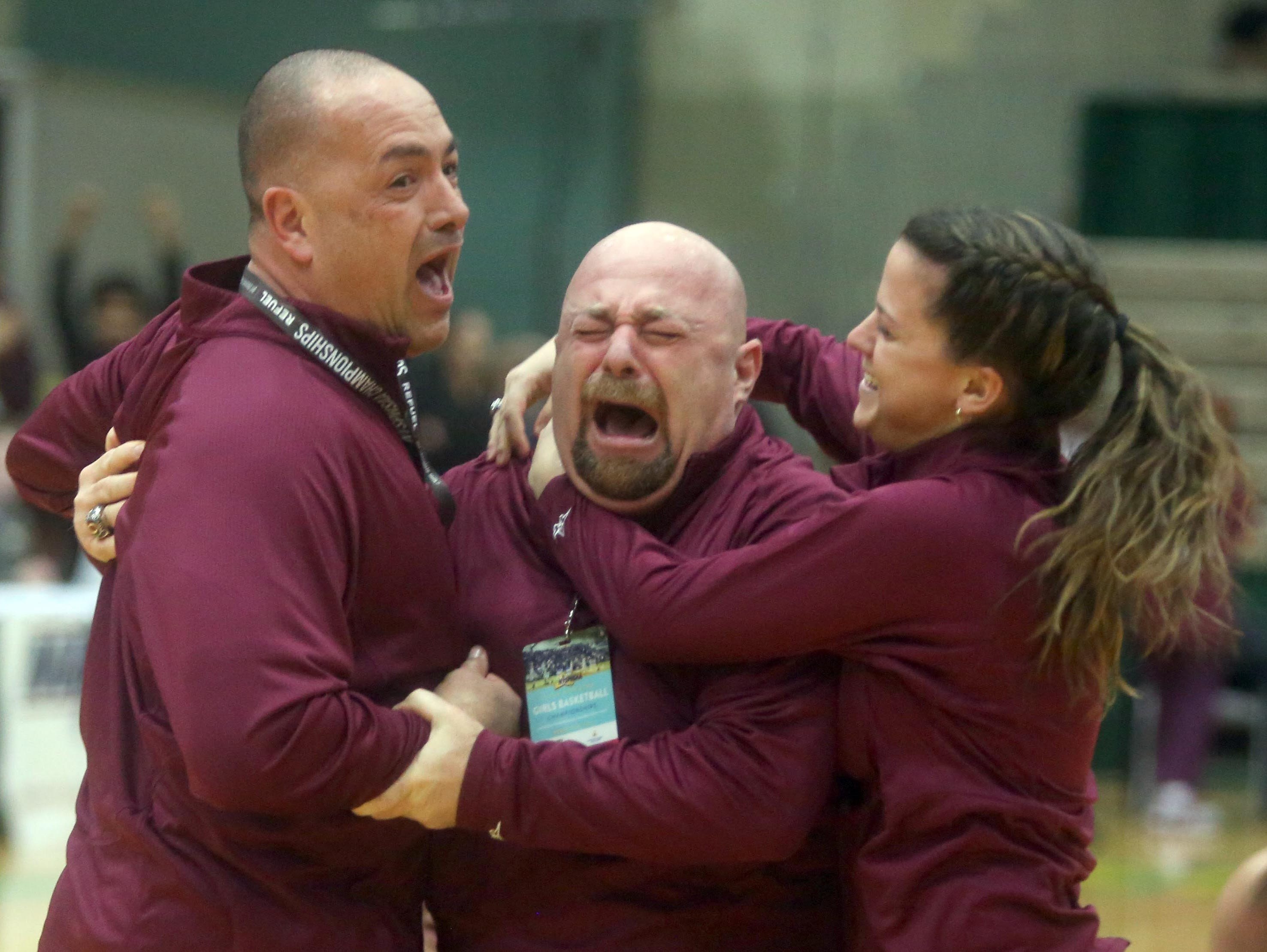 Ossining head coach Dan Ricci, center, celebrates with his assistant coaches after Ossining defeated Shenendehowa 69-66 to win the New York State Class AA championship at Hudson Valley Community College in Troy March 12, 2016.