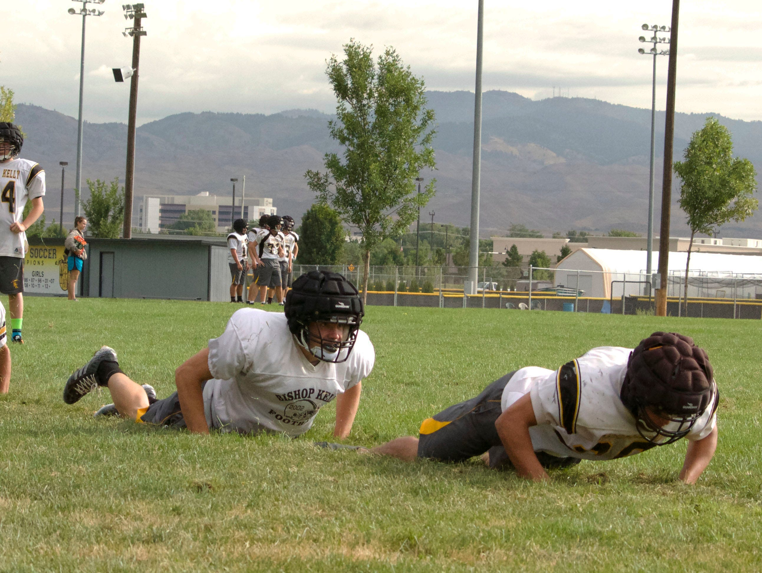 """Bishop Kelly football players wear """"Guardian Caps"""" during practice to help prevent concussions."""