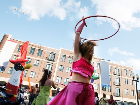 Lynn Spencer-Nelson (pink), of IndyHoopers, demonstrates her talent during the Fringe Opening Night Parade and Preview Party down Massachusetts Avenue Thursday, August 20, 2009.  Danese Kenon/The Star