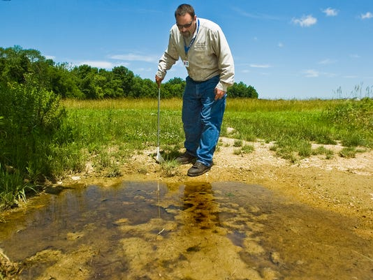 Adams County Conservation District's West Nile Virus coordinator Matt Stough searches a pool of standing water for mosquito larva samples outside of Allwood Manor subdivision in McSherrystown in this 2012.