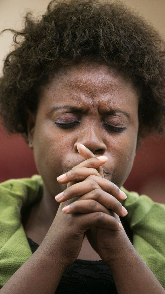Cecelia Nagbe puts her hands to her face while she prays  during a Prayer against Ebola at Africa Faith Expressions Church in Phoenix, AZ on Sunday, Oct. 12, 2014.