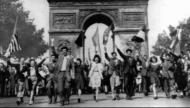 Parisians march through the Arc de Triomphe, jubilantly waving flags of the Allied Nations, as they celebrate the end of World War II on May 8, 1945. German military leaders signed an unconditional surrender in Reims, France, on May 7.