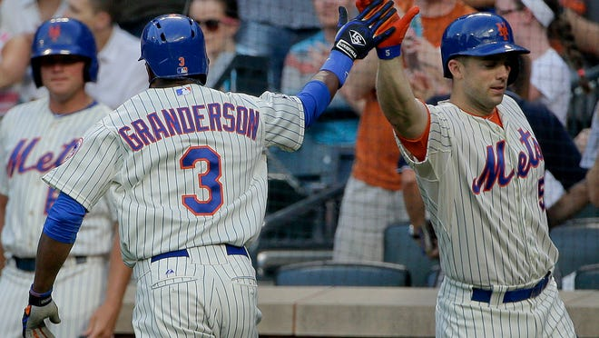 Mets right fielder Curtis Granderson (3) is greeted by teammate David Wright after hitting a solo home run against the Braves in the first inning Tuesday night.