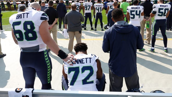 Seattle Seahawks' Michael Bennett remains seated on the bench during the national anthem before a game against the Green Bay Packers on Sept. 10, 2017 in Green Bay, Wis.