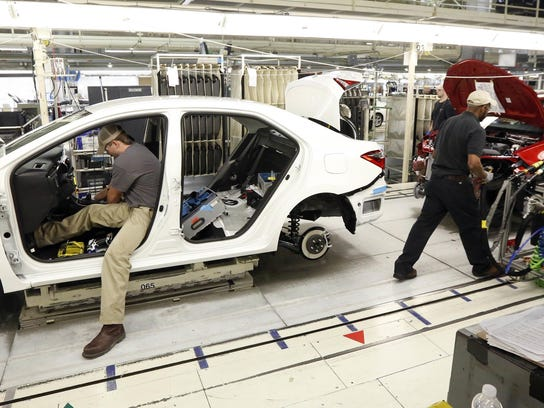 Technicians work on a Corolla assembly line at the