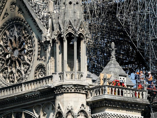 Firefighters and technicians work on a balcony of Notre-Dame