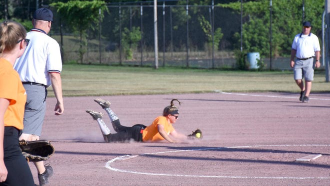 A Team Orsino infielder makes a diving catch at the back of the pitcher's circle with both umpires watching closely during the opening night of play in the Whalen Park Summer Fastpitch Softball League in Ilion.