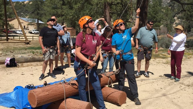 Pathfinder Ranch instructors Jane Mattione and Kayla Reece assist visitors up the climbing wall with belays.