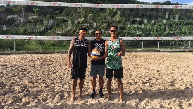 Josh Cruz, left and his partner Ryan Eugenio, right, are the last duo standing after winning the inaugural Liberation Day Beach Open. In the middle is Kaz Endo of the Guam Volleyball Federation which presented the event, sponsored by Calvo's Select Care and VIBE.