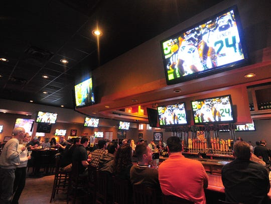 Football fans watch a game at Walk-On's Bistreaux &
