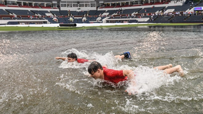 Jack Burkes, foreground, and Cole Catalano swim in the water in the outfield following heavy rainfall at Oxford-University Stadium before the start of the Missouri State vs. Tennessee Tech game for the NCAA Oxford Regional, in Oxford, Miss. on Friday, June 1, 2018. (Bruce Newman, Oxford Eagle via AP)