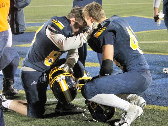 Tanner Allford, left, kneels with a teammate during
