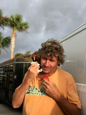 Chris Sidorski of Key West feeds Baby Chewbacca in the parking lot of the pet-friendly shelter at Liberty Magnet.