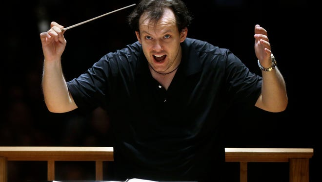 FILE -- In this Nov. 20, 2014 file photo, Boston Symphony Orchestra music director Andris Nelsons rehearses with the orchestra at Symphony Hall, in Boston. Nelsons has reached agreement on contract extensions with both the Boston Symphony Orchestra and the Gewandhausorchester of Leipzig, Germany, the parties announced on Monday, Oct. 5. With the three-year contract extension, Nelsons is to remain the BSO's music director through the the 2024-25 season.