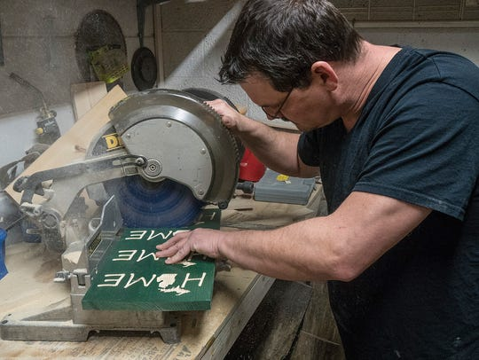 Jeff Powers cuts signs in his workshop next to the