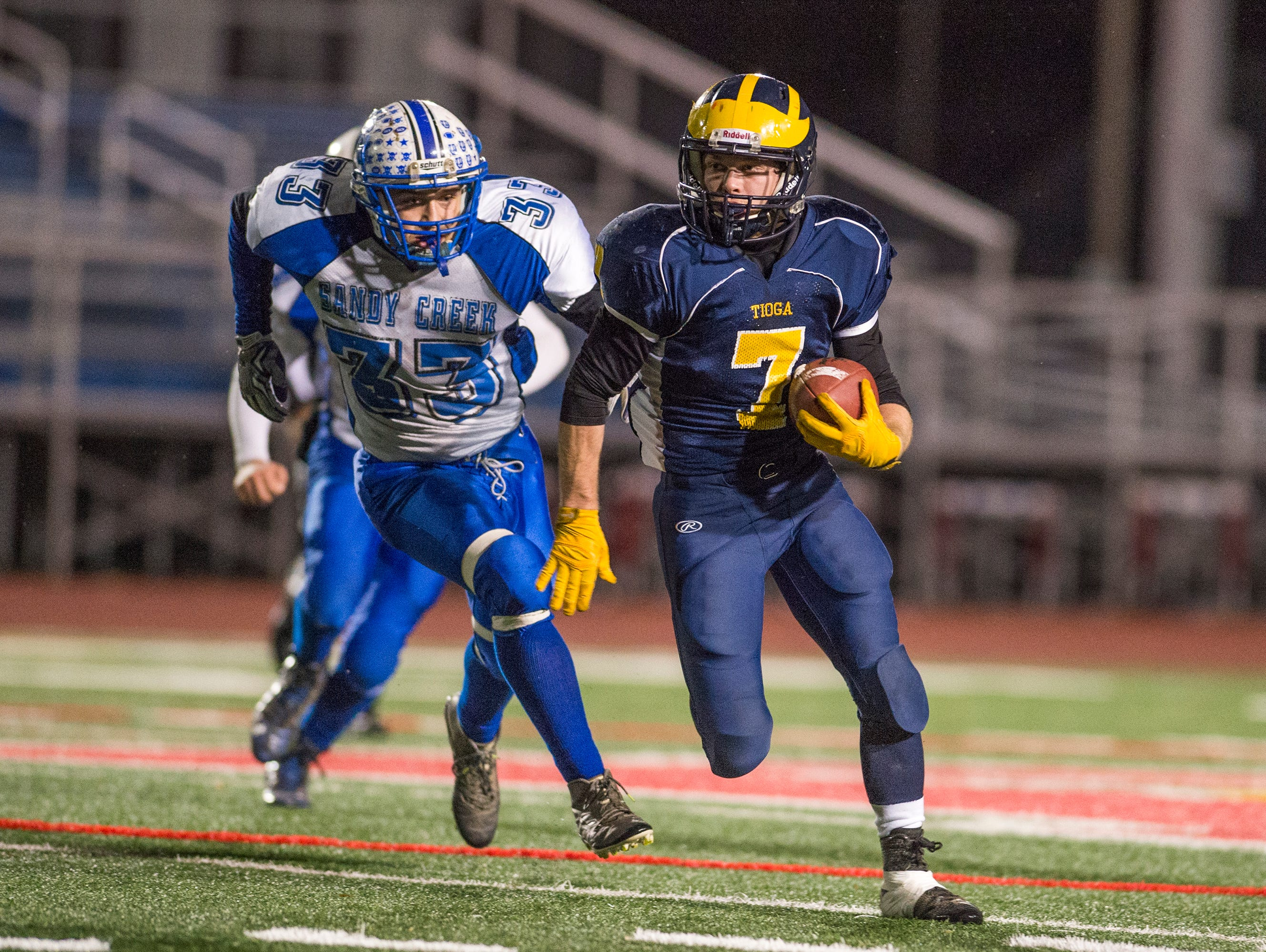 Tioga running back Jesse Manuel eludes Sandy Creek defenders during the second quarter of the Tiger's Class D state quarterfinal playoff game at Binghamton Alumni Stadium on Friday, Nov. 13, 2015.