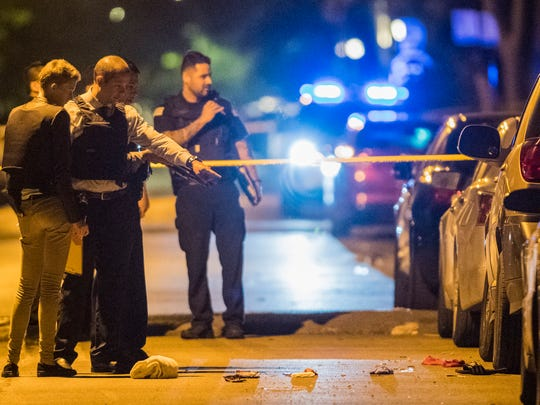 In thisJune 14, 2018, photo, Chicago police officers investigate the scene where two people were shot. A 12-year-old Michigan girl spending the summer in Chicago was fatally shot at the scene, hours after attending a cousin's eighth-grade graduation. Family members at the hospital identified the girl as She'nyah O'Flynn of Covert, Michigan. She and a man who was injured were apparently unintended victims of gunfire from a nearby party. Police say there have been no arrests.