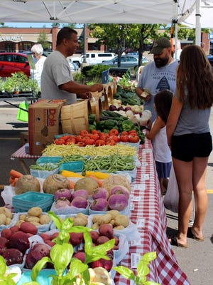 Shoppers visit a fresh vegetable vendor on a sunny summer morning at the Joe Obbie Farmers' Market in Webster, held every Saturday morning at Towne Center Plaza.