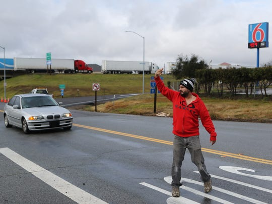 Carlos Ceron, a truck driver from Sacramento, helps another driver turn around Thursday on Twin View Boulevard in Redding. Ceron said he spent the night in his truck on the side of the Twin View on ramp and is on his way to Seattle.