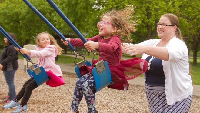 Candace Streng, a nanny battling cancer and dealing with expensive treatments, pushes 4-year-old Sarah Kovalik on the swing at McHattie Park in South Lyon Thursday, May 11, 2017, while 4 1/2-year-old Lila Scott watches. Streng is a nanny to Kovalik and her twin sister Emily, and meets with a moms group regularly, a group which is fundraising for Streng via a GoFundMe page and planning a June 17 fundraiser.