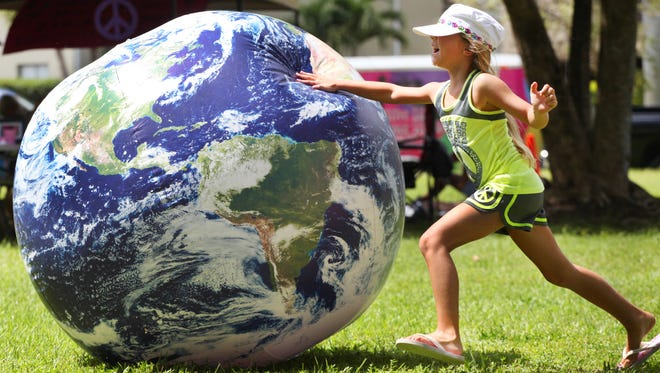 Genevieve Bailey, of Cape Coral, chases after an inflatable Earth at a past Peace Day in the Park at Jaycee Park in Cape Coral.