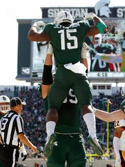 Michigan State's La'Darius Jefferson (15) is lifted by David Beedle as they celebrate Jefferson's touchdown against Central Michigan during the third quarter of an NCAA college football game, Saturday, Sept. 29, 2018, in East Lansing, Mich. Michigan State won 31-20. (AP Photo/Al Goldis)
