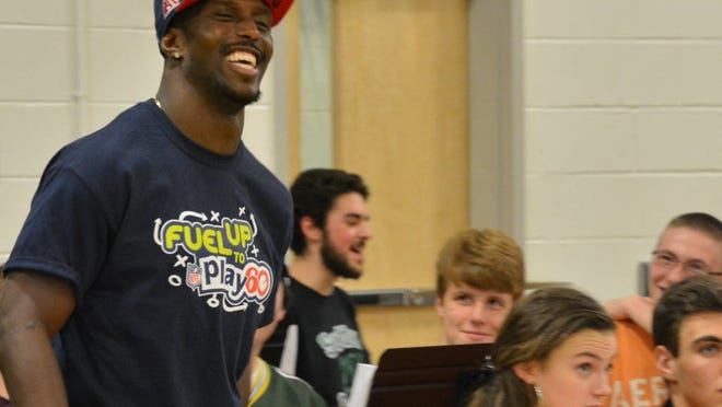 Devin McCourty shares a laugh with the Sutton High band during an appearance at the school in 2016.