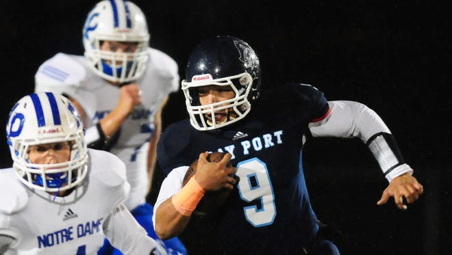 Bay Port quarterback Alec Ingold gets past Notre Dame's Vincent Pallini on a first quarter run during last week's game. The Pirates will not play at home this season until their new turf field is installed.